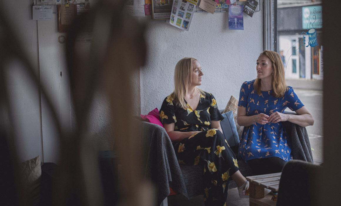 Two women sitting on a couch chatting to each other