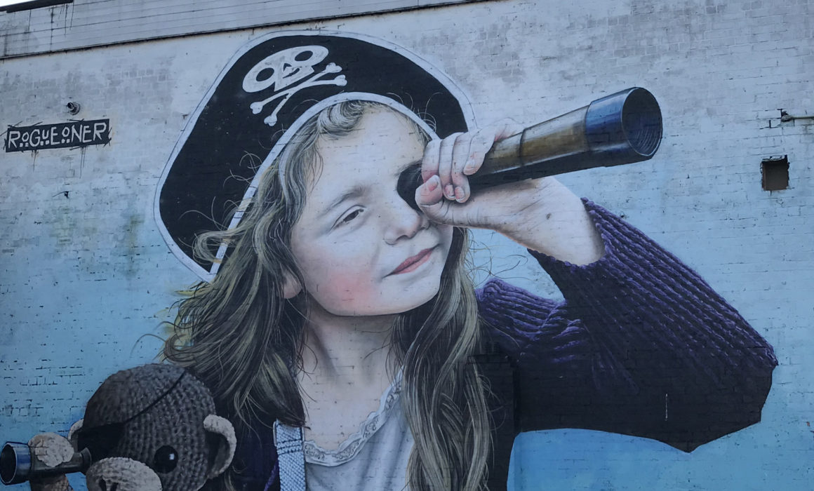 Street art of girl with pirate hat and telescope